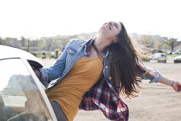 Ausgelassene junge Frau lehnt aus Autofenster
