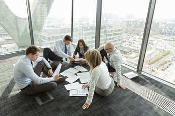 Geschäftsleute sitzen auf dem Boden diskutieren Papiere