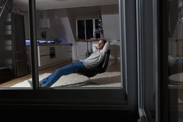 Mann zu Hause, Entspannen im Sessel in der Nacht