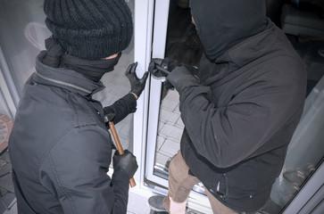 Zwei Einbrecher öffnen Terrassentür eines Einfamilienhauses