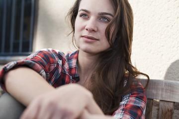 Entspannte junge Frau sitzt im Freien