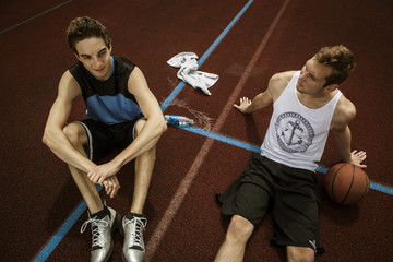 Portrait von zwei jungen Basketball-Spielern, entspannt auf Basketballplatz
