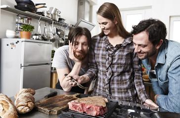 Freunde bei Zubereitung von Speisen in der Küche