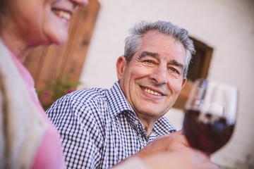 Senioren, Paar sitzt im Hof, trinkt Rotwein