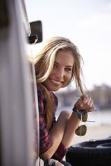 Lächelnde junge Frau schaut aus Minivan