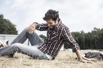 Lächelnder cooler Mann sitzt im Gras