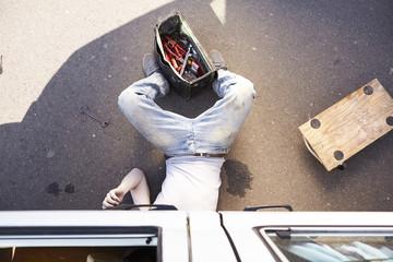 Mann liegt auf dem Boden, Reparatur Auto