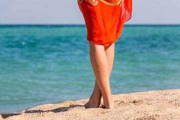 Beautiful woman's legs on sandy beach.
