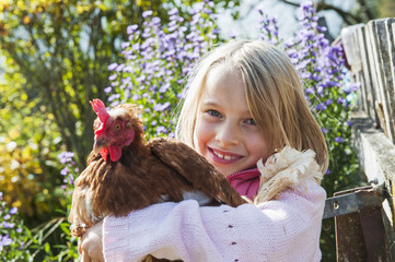 Glückliches Mädchen umarmt eine Henne