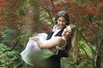 Bräutigam, der Braut im Garten trägt
