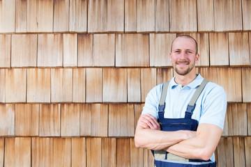 Zuversichtlicher Handwerker an Holzwand