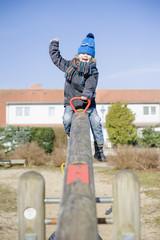 Deutschland, Mecklenburg-Vorpommern, Rügen, glücklicher kleiner Junge sitzt auf Wippe