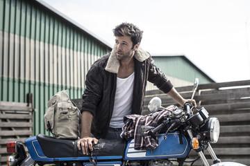 Portrait eines coolen Mannes, stützt sich auf Motorrad