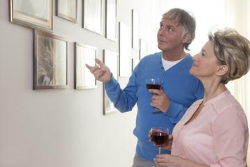 Älteres Ehepaar schaut sich Bilder im Haus von Freunden an