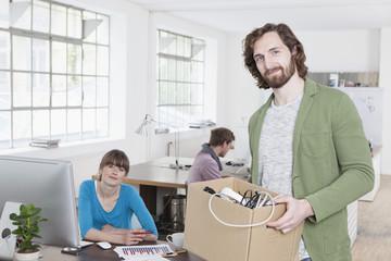 Junger Mann mit einem Karton von Stromkabeln in einem kreativen Büro