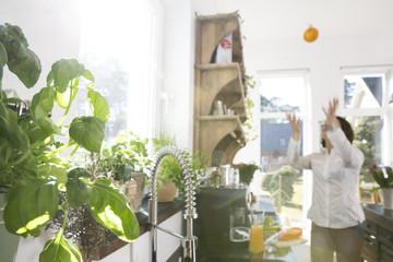 Frau in der Küche wirft Orange in die Luft
