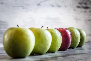 Roter Apfel in einer Reihe von grünen Äpfeln