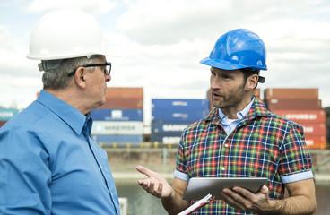 Zwei Männer mit Schutzhelmen im Gespräch bei Containerhafen