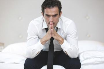 Geschäftsmann sitzt auf Hotelbett