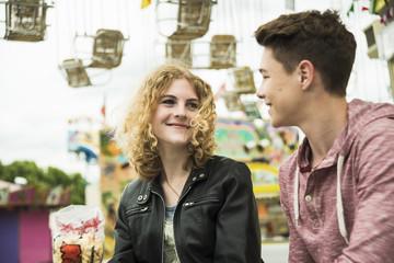 Teenager-Paar auf Kirmes, Kettenkarussell im Hintergrund