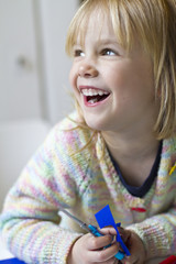Lächelndes Mädchen mit Schere und Buntpapier