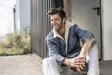 Lachender cooler Mann mit Jeansjacke