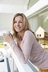 Frau mit einer Tasse Kaffee am Geländer