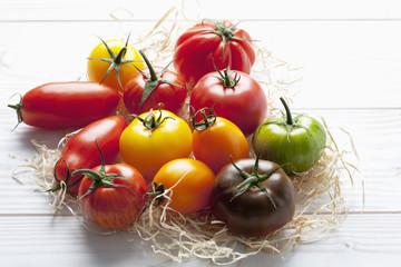 Verschiedene Tomaten auf Holzwolle und Holztisch