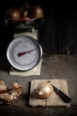 Zwiebel und Messer auf Schneidebrett, Küchenwaage mit Zwiebeln im Hintergrund
