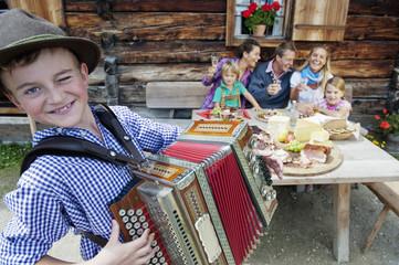Österreich, Salzburger Land, Altenmarkt-Zauchensee, Familie bei Picknick, Junge spielt Akkordeon