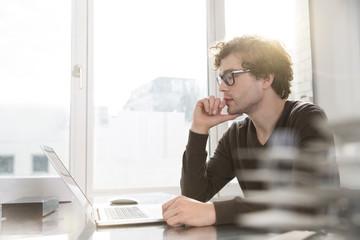 Porträt des jungen Architekten mit Laptop in seinem Büro