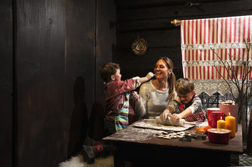 Mutter und ihre zwei kleinen Söhne backen in der Weihnachtszeit Plätzchen