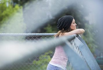 Mädchen mit Wollmütze lehnt an einem Drahtzaun
