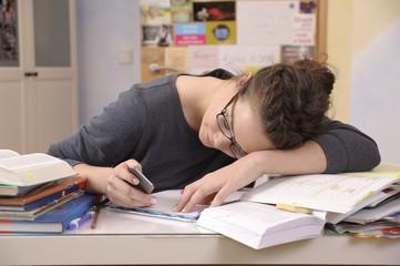 Schülerin mit Smartphone an ihrem Schreibtisch