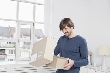 Mann beim Auspacken eines Kartons
