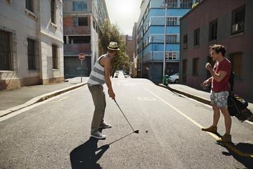 Zwei Freunde spielen Crossgolf in der Stadt