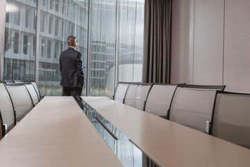 Geschäftsmann schaut aus dem Fenster im Konferenzraum im Hotel