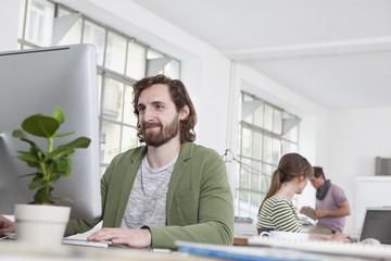 Porträt der jungen Menschen arbeiten am Computer in einem kreativen Büro