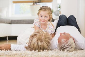 Älteres Paar, Enkelin auf dem Boden liegend
