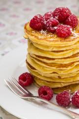 Stapel von Pfannkuchen mit Honig, Himbeeren und Puderzucker