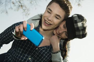 Porträt von Teenager-Paar, fotografieren sich mit Smartphone, Selfie