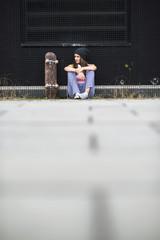 Mädchen mit Skateboard sitzt vor einer schwarzen Fassade