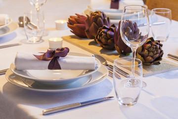Gedeck und Dekoration mit Artischocken auf festlich gedecktem Tisch
