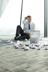 Geschäftsmann sitzt auf Büroetage von zerknittertem Papier umgeben