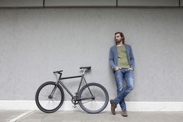 Junger Mann, der neben seinem Rennrad lehnt, an einer Wand