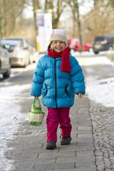 Kleines Mädchen mit Tasche auf dem Bürgersteig