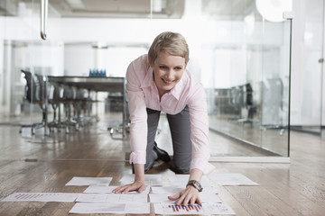 Geschäftsfrau im Büro, Sortieren von Papiere auf dem Boden