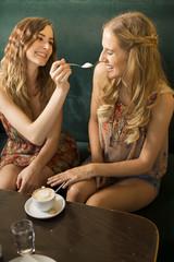 Zwei Freundinnen, die Spaß in einem Café haben
