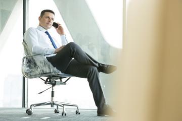 Geschäftsmann mit Handy auf dem Bürostuhl eingewickelt