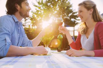 Paar stößt an, mit Rotweingläsern am Tisch im Abendlicht